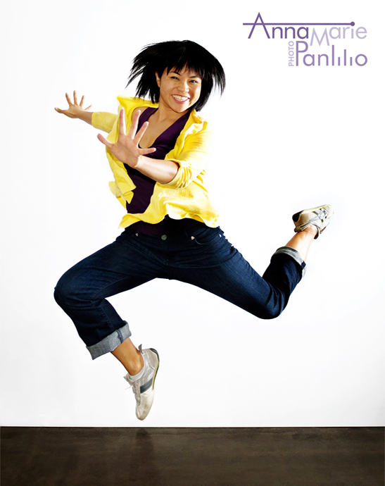 Anna Marie jumping for joy, wearing purple and gold