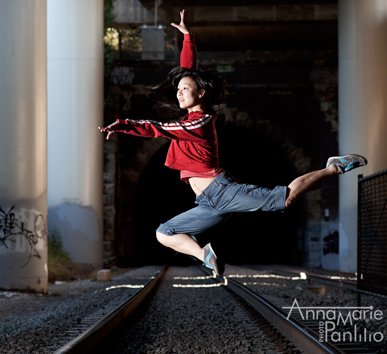 Kira leaps above railroad tracks.