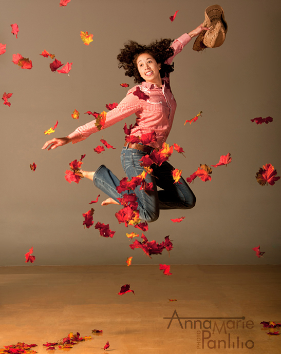Cowgirl Jeanine jumping through autumn leaves