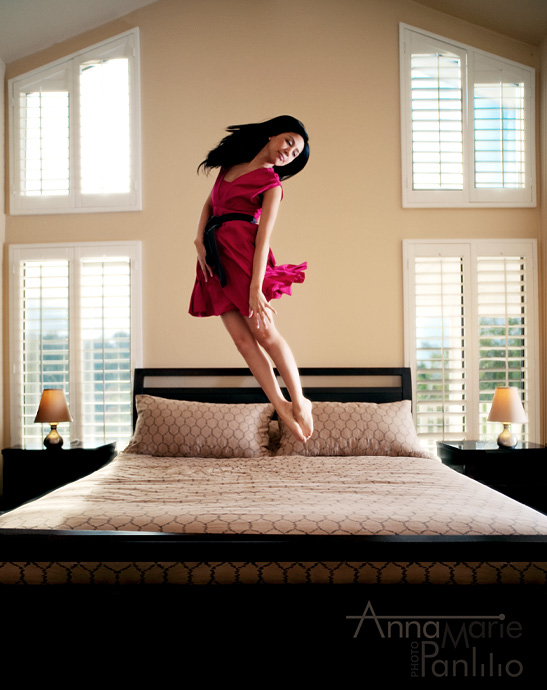 Charlene jumps on bed with sun streaming into windows