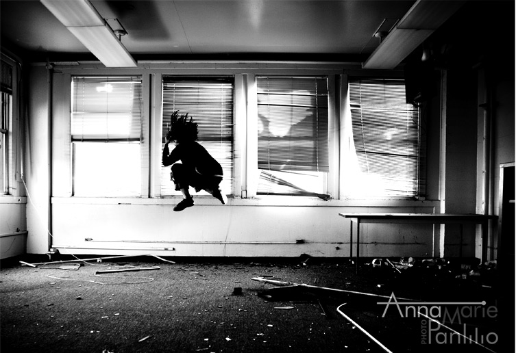 AM jumps in abandoned classroom, black and white