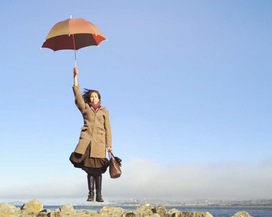 Jeanine levitates over the San Francisco Bay with umbrella and bag.